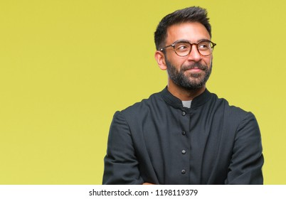 Adult hispanic catholic priest man over isolated background smiling looking side and staring away thinking.