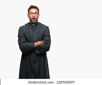 Adult hispanic catholic priest man over isolated background afraid and shocked with surprise expression, fear and excited face.