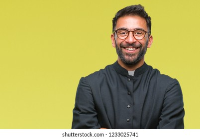 Adult hispanic catholic priest man over isolated background happy face smiling with crossed arms looking at the camera. Positive person.