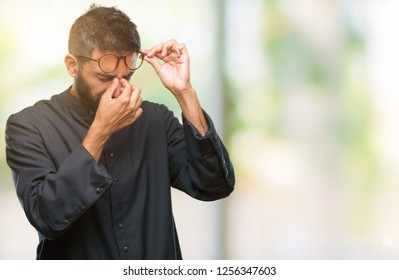 Adult hispanic catholic priest man over isolated background tired rubbing nose and eyes feeling fatigue and headache. Stress and frustration concept.