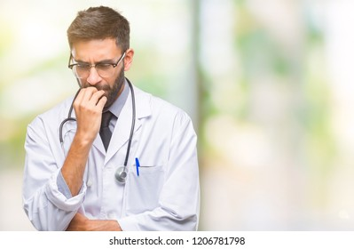 Adult hispanic doctor man over isolated background looking stressed and nervous with hands on mouth biting nails. Anxiety problem.