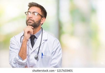 Adult hispanic doctor man over isolated background with hand on chin thinking about question, pensive expression. Smiling with thoughtful face. Doubt concept.