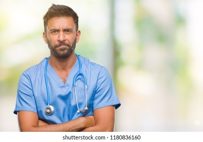 Adult hispanic doctor or surgeon man over isolated background skeptic and nervous, disapproving expression on face with crossed arms. Negative person.