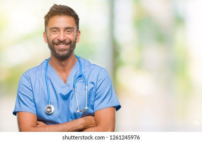 Adult hispanic doctor or surgeon man over isolated background happy face smiling with crossed arms looking at the camera. Positive person.
