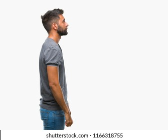 Adult hispanic man over isolated background looking to side, relax profile pose with natural face with confident smile.