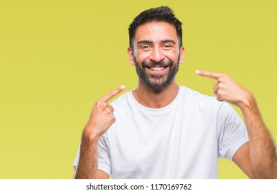 Adult hispanic man over isolated background smiling confident showing and pointing with fingers teeth and mouth. Health concept.