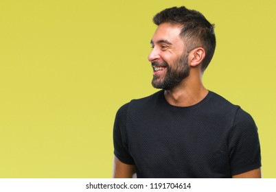 Adult hispanic man over isolated background looking away to side with smile on face, natural expression. Laughing confident.