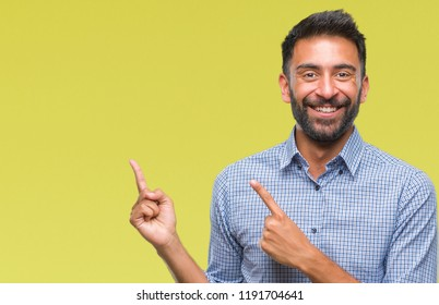 Adult hispanic man over isolated background smiling and looking at the camera pointing with two hands and fingers to the side.