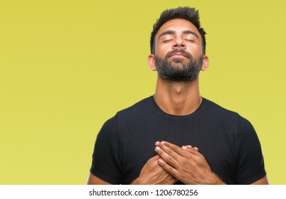 Adult hispanic man over isolated background smiling with hands on chest with closed eyes and grateful gesture on face. Health concept.