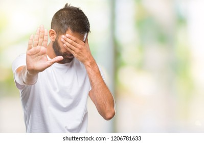 Adult hispanic man over isolated background covering eyes with hands and doing stop gesture with sad and fear expression. Embarrassed and negative concept.