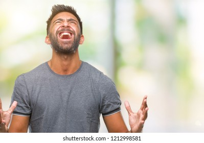 Adult hispanic man over isolated background crazy and mad shouting and yelling with aggressive expression and arms raised. Frustration concept.