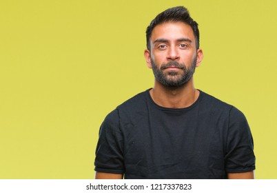 Adult hispanic man over isolated background with serious expression on face. Simple and natural looking at the camera.