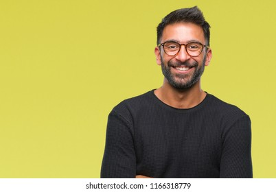 Adult hispanic man wearing glasses over isolated background happy face smiling with crossed arms looking at the camera. Positive person.