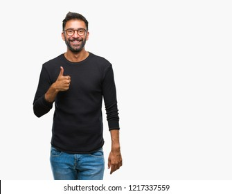 Adult hispanic man wearing glasses over isolated background doing happy thumbs up gesture with hand. Approving expression looking at the camera with showing success.