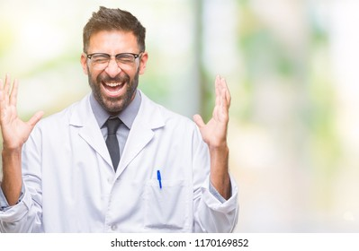 Adult hispanic scientist or doctor man wearing white coat over isolated background celebrating mad and crazy for success with arms raised and closed eyes screaming excited. Winner concept