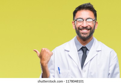 Adult hispanic scientist or doctor man wearing white coat over isolated background smiling with happy face looking and pointing to the side with thumb up.