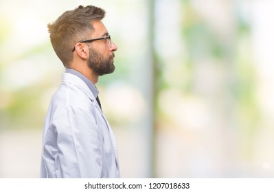 Adult hispanic scientist or doctor man wearing white coat over isolated background looking to side, relax profile pose with natural face with confident smile.