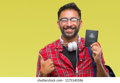 Adult hispanic student man holding passport of australia over isolated background happy with big smile doing ok sign, thumb up with fingers, excellent sign