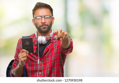 Adult hispanic student man holding passport of australia over isolated background pointing with finger to the camera and to you, hand sign, positive and confident gesture from the front