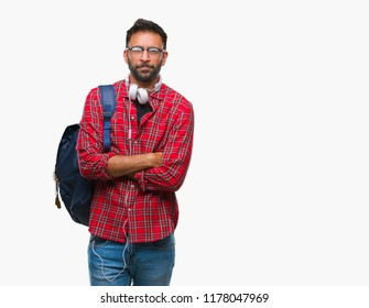 Adult hispanic student man wearing headphones and backpack over isolated background skeptic and nervous, disapproving expression on face with crossed arms. Negative person.