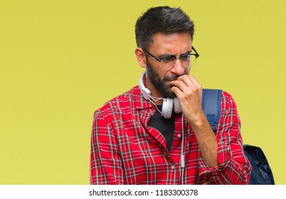 Adult hispanic student man wearing headphones and backpack over isolated background looking stressed and nervous with hands on mouth biting nails. Anxiety problem.