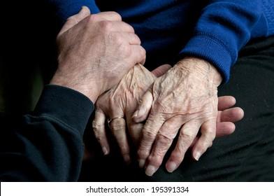 adult holding senior hands