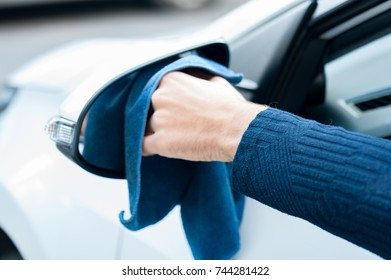 Adult human hand with blue microfiber cloth is cleaning the mirror. Clean car concept.Side view of male hand from window