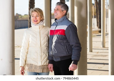 Adult husband and wife are walking together clear sunny day between columns
