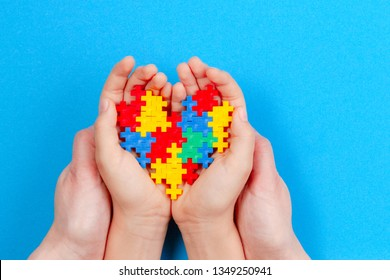 Adult and kid hands holding colorful heart on blue background. World autism awareness day concept
