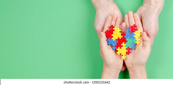 Adult and kid hands holding colorful heart on green background. World autism awareness day concept