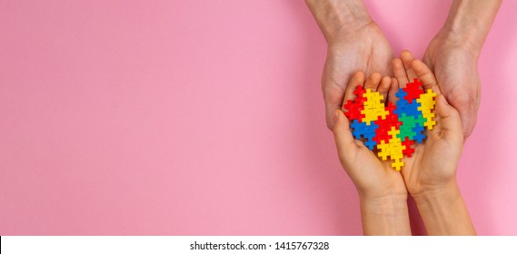 Adult and kid hands holding colorful heart on light pink background. World autism awareness day concept