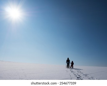 Adult and kid snowshoeing in the sunlight