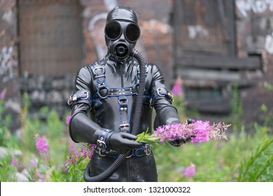 Adult kinky man dressed in fetish latex rubber costume with kinky mask