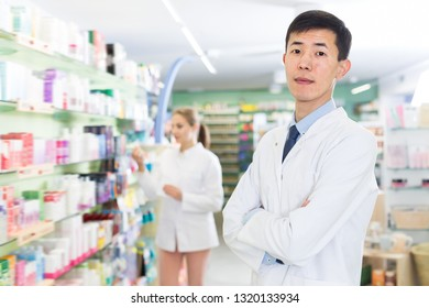 Adult korean man pharmacist is standing with medicines in pharmacy