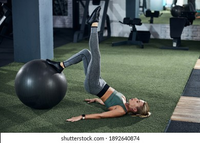Adult lady lying on her back and putting one leg on a stability ball while stretching another in the air