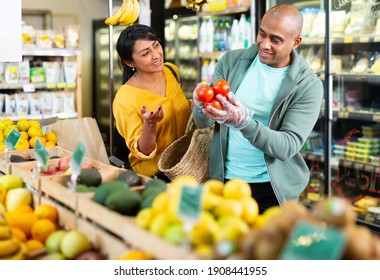 Adult latin american married couple shopping together in grocery store, choosing fresh tomatoes..