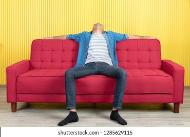 Adult look like feels tired and alone appearance sitting on red sofa, arms wide spread turn face up in modern living room, bright yellow stripe wall background. Concept for exhausting, onerous man.
