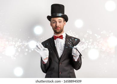 adult magician with shrug gesture holding wand on grey with glowing illustration