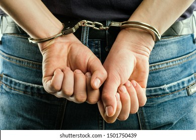 Adult male arrested and handcuffed.Man under Arrest. Hands with handcuffs in the front.Man with his hands handcuffed in criminal concept.
