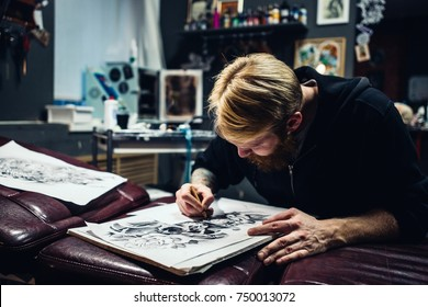Adult male artist draws a picture of a pencil
