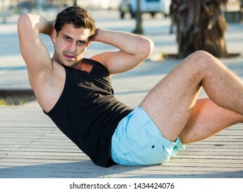 Adult male athlete doing situps outdoors in sunny morning