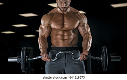 Adult male bodybuilder posing in the gym and perform various exercises