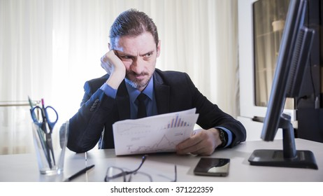 adult male businessman thinking in a bad mood sitting at a Desk in a gloomy office