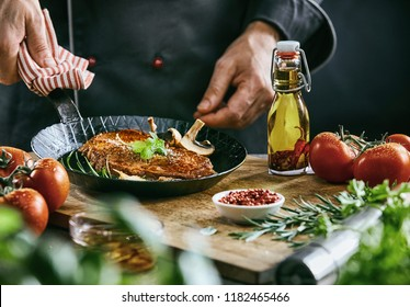 Adult male chef in black suit holding dark metal skillet while dropping mushrooms into pan with seasoned steak