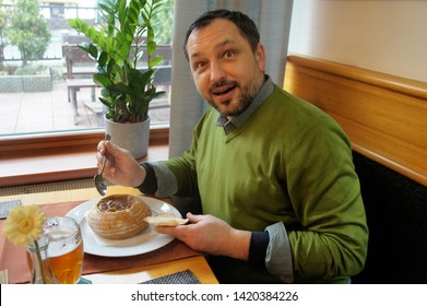 Adult male delighted with traditional Czech dish goulash in bread sits at a table in a cafe