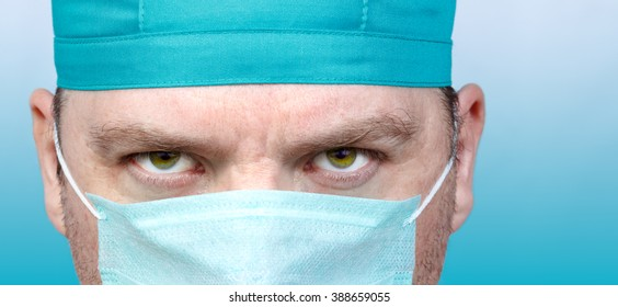 Adult male doctor portrait close up on blue background