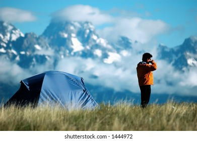 adult male drinking coffee next to his tent