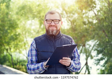 Adult male ecologist with glasses. Man writes information about environmental problems while standing against a background of green plants.