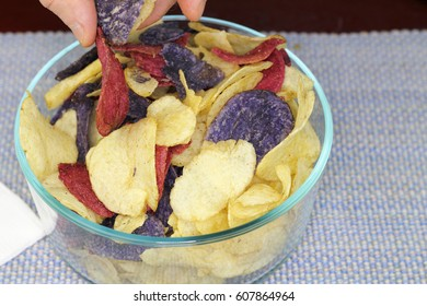 Adult male fingers picking up one of each of three colors of potato chips. Yellow, red and purple potato chips chosen by fingers of an adult male.