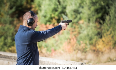 Adult male with a handgun at the outdoor shooting range